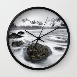 Mountain range in front of wild surf Wall Clock