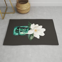 Magnolia in a glass jar with black background Rug