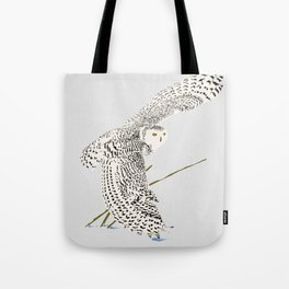 The snowy owl in flight with his wing touching the snow Tote Bag