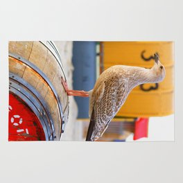 Seagull on the beach on a wooden barrel Rug