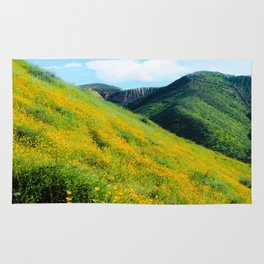 yellow poppy flower field with green leaf and green mountain and cloudy blue sky in summer Rug