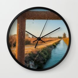 Bridge over an irrigation channel of the Lomellina at sunset Wall Clock