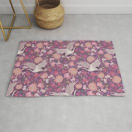 Cranes with chrysanthemums and pink magnolia on purple background Rug