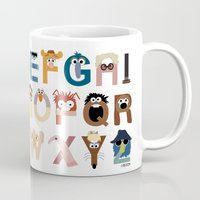 leaves Mugs featuring Muppet Alphabet by Mike Boon