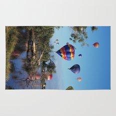 Hot air balloons over lake Rug