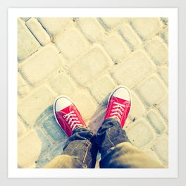 young man feet in red sneakers on cobbled road Art Print