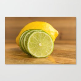 Lime slices cross section on wood close front view Canvas Print
