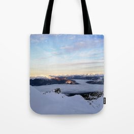 Morning light sweeping mountain peaks above sea of clouds Tote Bag