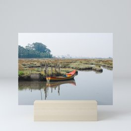 Colorful small boat docked near shore on rickety pier. Still water with reflections in Aveiro Lagoon Mini Art Print