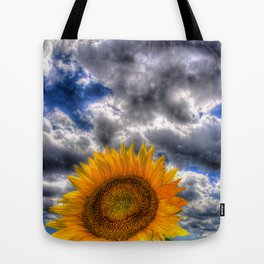 Clouds drift over a sunflower field Tote Bag