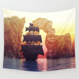 A pirate ship off an island at a sunset Wall Tapestry