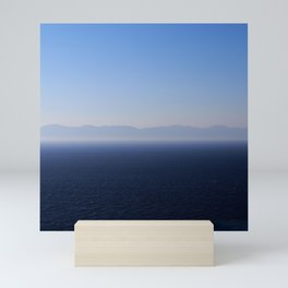 Sea with mountains silhouette and clear blue sky background  Mini Art Print