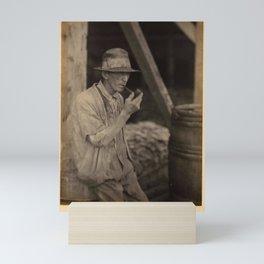Doris Ulmann  (1882–1934), Elderly man in ragged hat, sweater, and overalls, leaning against barrel, Mini Art Print