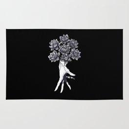 Hand with lotuses on black Rug