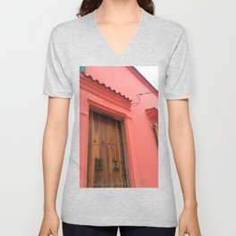 Cartagena is Peachy, Colombia, South America. Coral Pink Building with Ornate Lizard design Unisex V-Neck