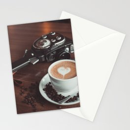 A cup of hot cappuccino placed on a table next to the old camera with lens and coffee beans Stationery Cards