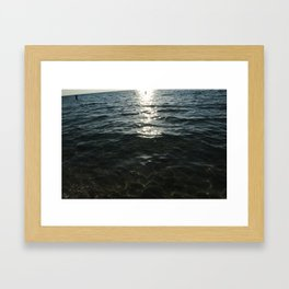 Woman walking into the ocean Framed Art Print