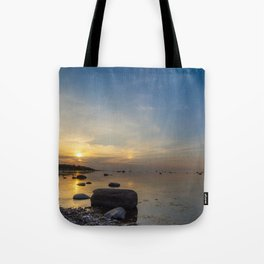 Sun with faint halo over the calm sea and reef rocks Tote Bag
