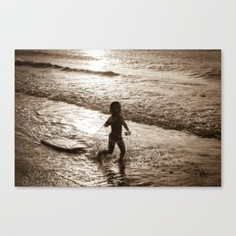 Little surfer girl runs in the waves with her bodyboard Canvas Print