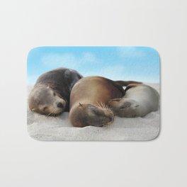 Sea lions family sleeping together on beach Bath Mat