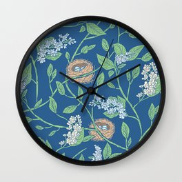 Branches with flowers and bird nests on blue background Wall Clock