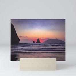 Red sunset behind coastal rock Mini Art Print