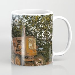 Old tractor on a pebble beach by a river Coffee Mug