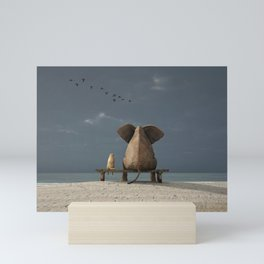elephant and dog sit on a beach Mini Art Print