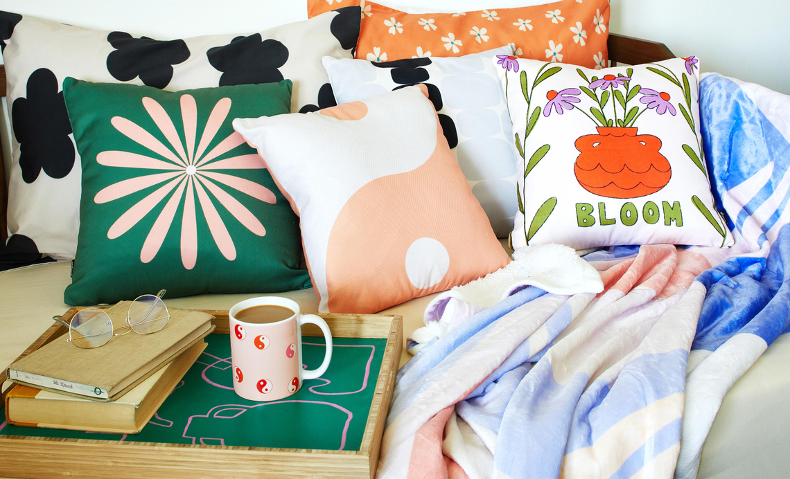 day bed with pillows, blankets, serving tray and mug