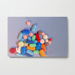 Pills of various colors on a blue neutral background Metal Print