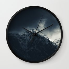 Darkness and storm clouds over mountains Wall Clock