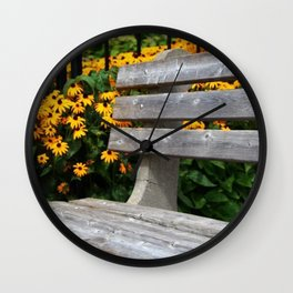 Seat in the park with yellow flowers Wall Clock