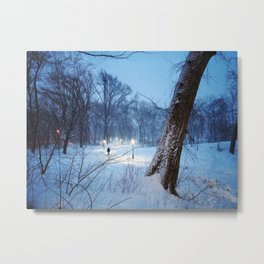 A man walking on a lit path through the snow in Central Park Metal Print