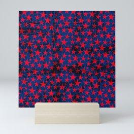 Red stars on grunge textured blue background Mini Art Print