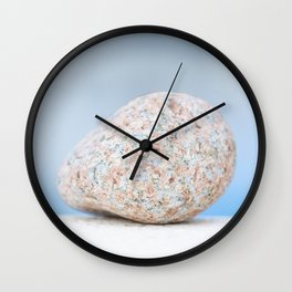 Granite pebble with blue water background Wall Clock