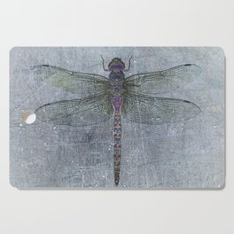 Dragonfly on blue stone and metal background Cutting Board