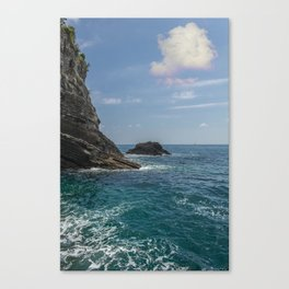 rocky cliff by the sea and a huge cottony cloud in the sky above a small imperceptible boat Canvas Print