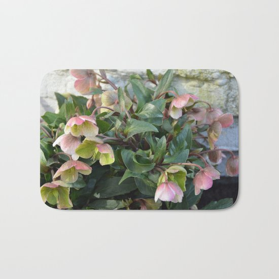 Pink flowers against an old brick wall Bath Mat