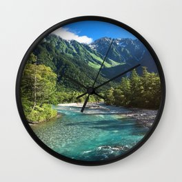River flowing in front of snow covered mountain Wall Clock