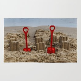 sandcastles and red spades on the beach Rug