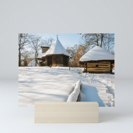 Snow cover in a Romanian Village with an old wooden church Mini Art Print
