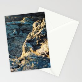 The sun is setting over the rocks Stationery Cards
