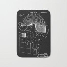 Slinky: Richard T. James Slinky Patent - White on Black Bath Mat