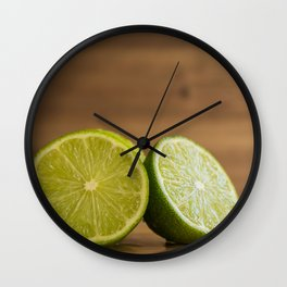Two lime halves on rustic wood close front view Wall Clock