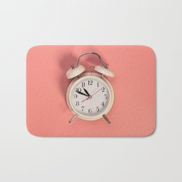 White alarm clock on pink background Bath Mat