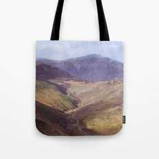 Distant tracks leading up a mountainside in Autumn. Cmbria, UK. (Shot on film). Tote Bag