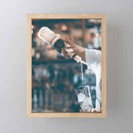 Bartender prepares a cocktail in the nightclub. Expert barman is making cocktail at night club. Framed Mini Art Print
