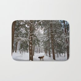 Dog exploring a snowy forest Bath Mat