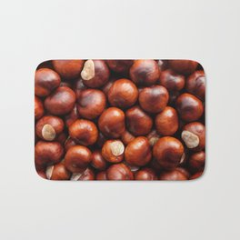 Shiny red-brown conkers in fall Bath Mat