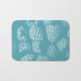 Raspberries in blue Bath Mat